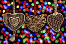 Three Hearts Made From Natural Materials (wood Twigs) Against The Background Of A Colorful Bokeh.