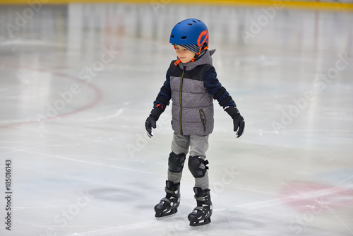 Fotografía Adorable little boy in winter clothes with protections skating on ice rink