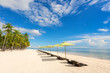 Beautiful beach with sunbeds, umbrellas and palms. Blue sky with clouds and sea on background.