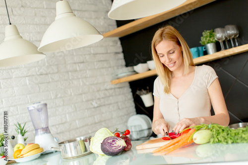 Staande foto Koken Pretty young woman preparing healthy meal in the kitchen