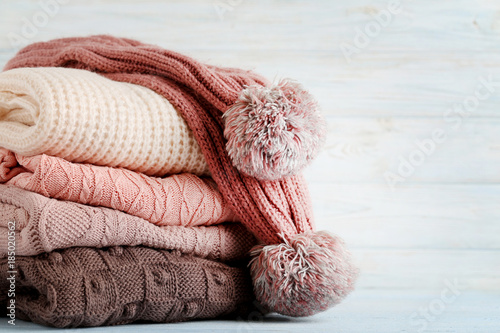 Foto  Stack of knitted sweaters and scarf on wooden table