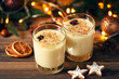 Eggnog in glasses with star anise and cookies on wooden table