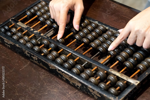 Closed up of business woman hand that calculate with wood abacus (Traditional ch Wallpaper Mural