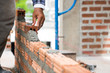 Brickwork walls, technicians are forming brick walls with mortar (cement, sand) by using a trowel as tools in Project House construction