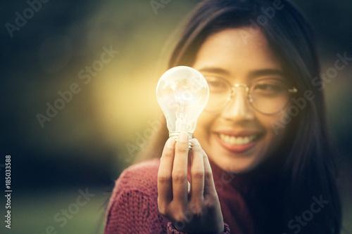Fotografie, Obraz  A young girl get a brilliant idea, use bulb as icon