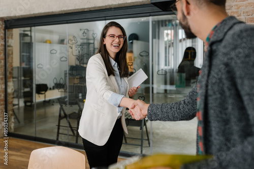 Smiling plainly and firmly handshaking with human resource manager