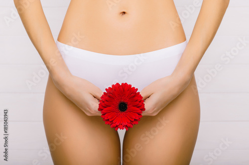 slim woman dressed in white panties, holding a red flower in her hands, close-up. Gynecology, menstruation, the concept of genital health