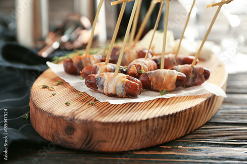 Fotografía  Wooden board with bacon wrapped dates on table
