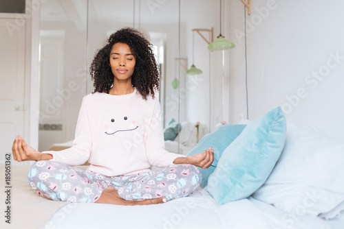 Carta da parati Happy beautiful young black woman relaxed  at home doing morning meditation in bed