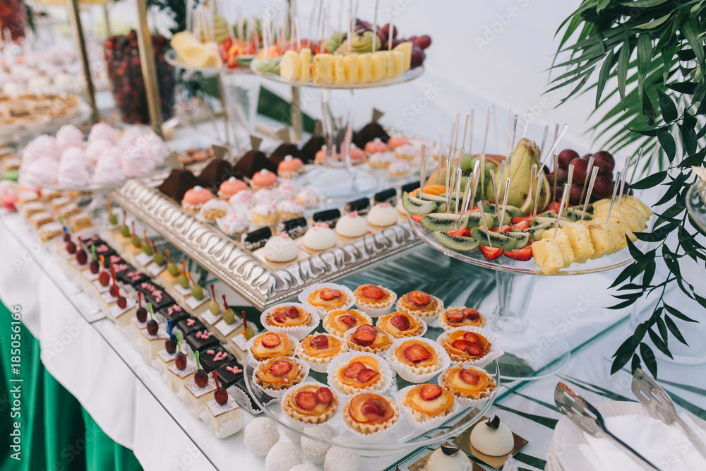 Fototapeta Beautiful wedding sweet buffet with decor and green.