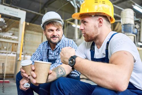 Fotografie, Obraz  Portrait of two builders wearing hardhats taking break from work drinking coffee