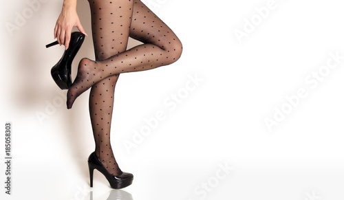 Foto Sexy woman legs in dotted pantyhose and black high heels, copy space, taking one