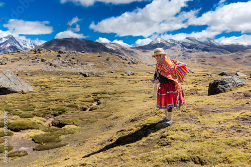 Photo Peruvian indigenous old woman standing weaving traditional cloths, Peru