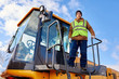 Low angle portrait of bearded worker standing on heavy yellow truck posing looking at camera against cold blue sky
