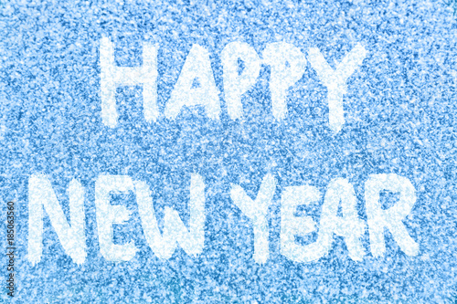 happy new year text message hand written on blue ice frosted window background in white snow