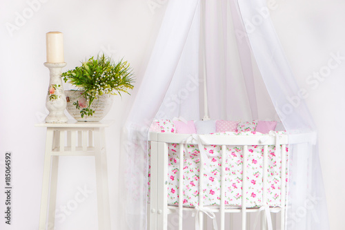 Crib. A cot for a child with a white canopy. Children's furniture.