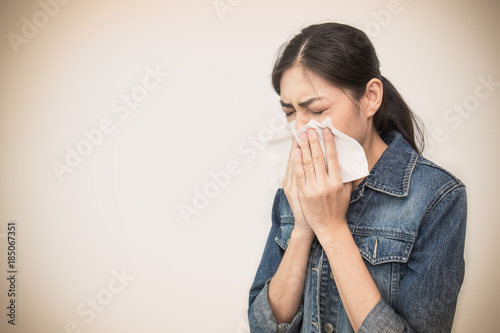 Fotografia, Obraz Woman with a cold blowing her runny nose with tissue