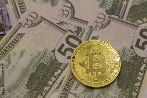 фотография  New banknotes of US dollars and a gold coin of crypto currency on a white background