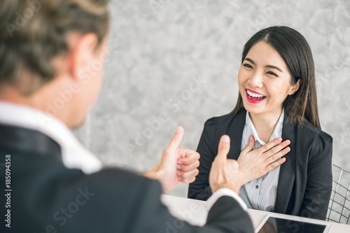 Photo Boss/Business man employer admires young Asian business woman/staff/employee by thumb up and clap with smiling face for her success and good/best in work and recognition/appreciate