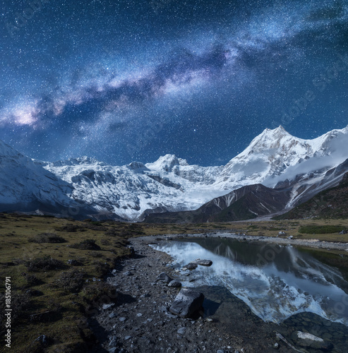 Foto auf Gartenposter Reflexion Milky Way and high mountains. Night landscape with mountains and starry sky reflected in water in Nepal. Lake, rocks with snowy peak and sky with stars. Himalayas. Fantastic scene with milky way
