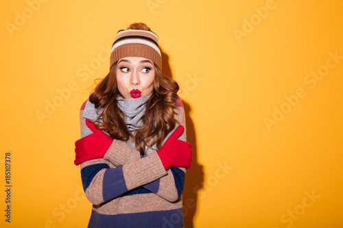 Portrait of a pretty frozen girl dressed in winter clothes