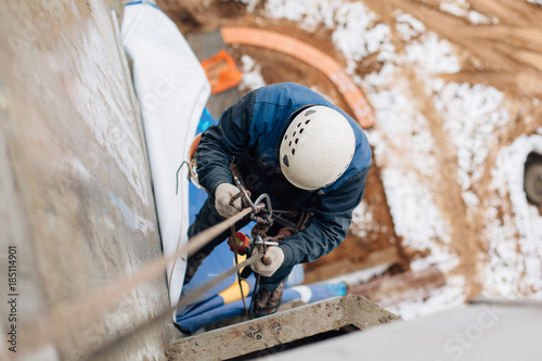Photo Professional industrial climber in helmet and uniform works at height