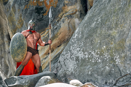 Fényképezés  Full length shot of a medieval warrior in battledress holding a shield and a spear standing on top of the rock looking away copyspace safety guard protection bravery muscles athletic body
