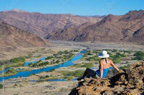 A female hiker enjoying the sun and view of a winding river through a harsh rock Canvas Print