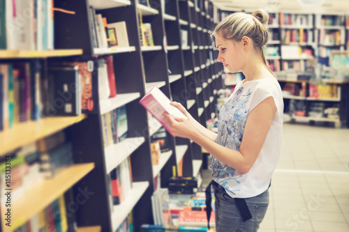 Photographie  young woman choosing a book to buy in bookstore