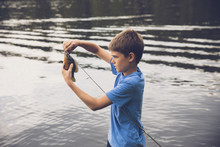 Side View Of Boy Removing Fish...