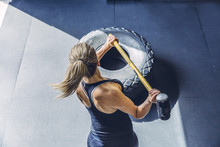High Angle View Of Woman Hammering Tire While Exercising In Gym