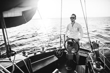 Black And White Photo On Which A Young Handsome Guy In Glasses Stands At The Helm Of The Yacht