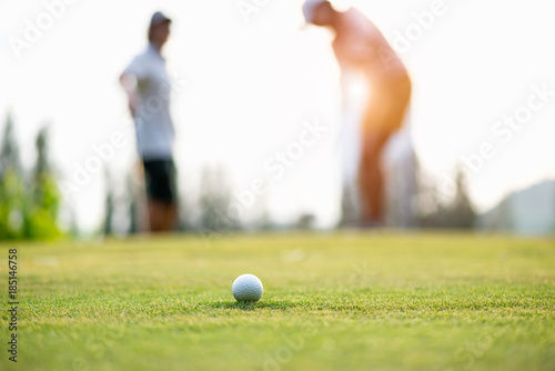 Deurstickers Golf Golf ball approach to the hold on the green. Couple golf player putting golf ball in the background. Lifestyle Concept.