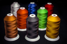 Several Of Multi-colored Spools Of Threads On A Black Background