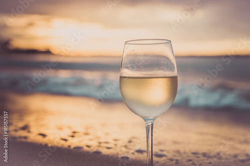 Fototapeta A glass  of white wine on the beach at sunset. Travel vacations concept. obraz