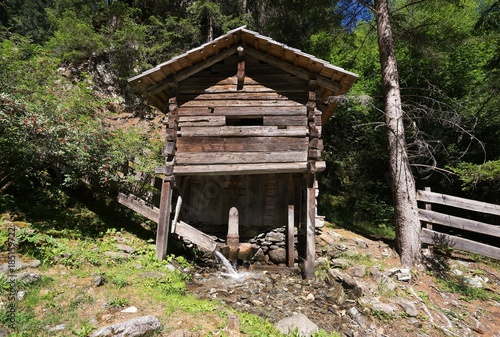 Photo  Restored or renovated old mediaeval wooden watermill or water mill in Austrian alps or alpine region tirol or carinthiha powered by mountain stream