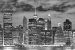 Black and white picture of New York City illuminated skyscrapers at night, USA.