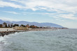 winter coast of the city of Sochi. Stone coast of the beach and house in the distance.