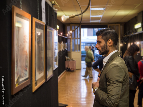 Valokuva  Side view of trendy confident man exploring art pieces in gallery