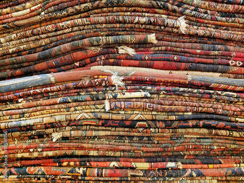 Fotografie, Obraz  Stack of colorful handmade antique Oriental style rugs and carpets background te