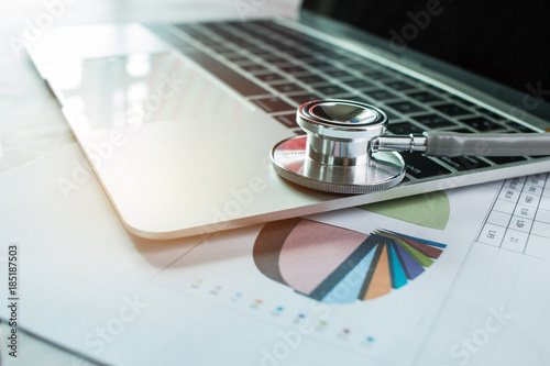 Fotografiet  Focus Stethoscope Doctor table on laptop computer with report analysis and money about Healthcare costs and fees in medical hostpital office