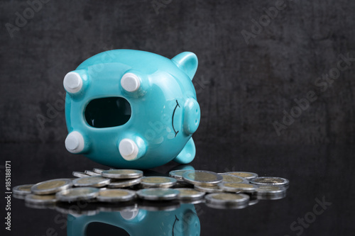 Photo  Saving money problem with empty piggy bank lay on dark black table with coins us
