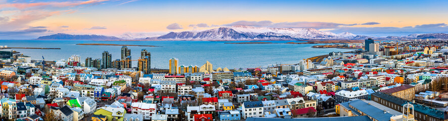 Aerial panorama of downtown Reykjavik at sunset with colorful houses and snowy mountains in the background