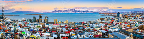 plakat Aerial panorama of downtown Reykjavik at sunset with colorful houses and snowy mountains in the background