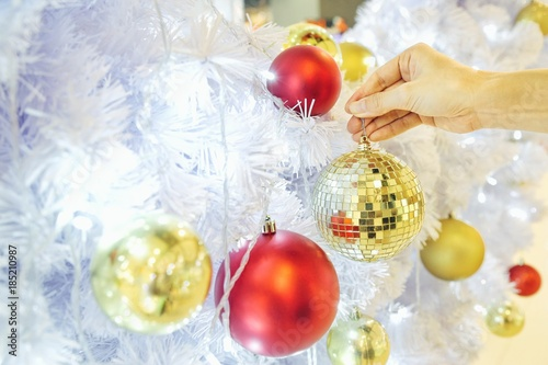 Closeup Image Of A Hand Decorating White Snow Christmas Tree With
