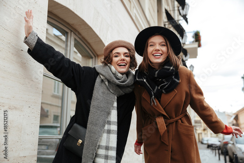 Stampa su Tela Portrait of two cheery girls dressed in autumn clothes walking
