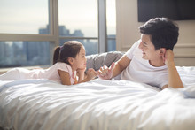 Cheerful Young Father Making A Pinky Swear With His Daughter On Bed