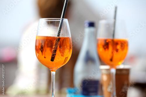 Zwei Cocktail-Gläser mit orange-farbenem Getränk ähnlich Aperol vor unscharfem Hintergrund Wallpaper Mural