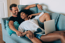 Happy Young Couple Relaxed At Home Lying Down In The Couch On The Computer