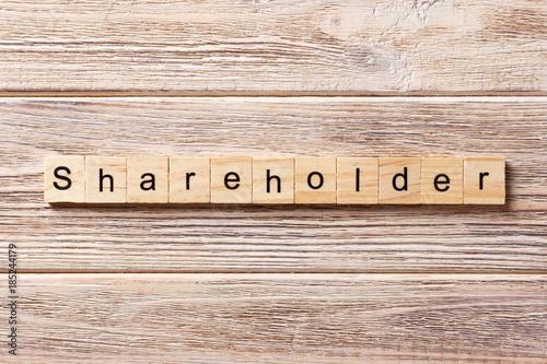 Fotomural shareholder word written on wood block